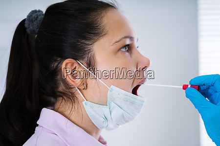 doctor taking mouth fluid swab sample