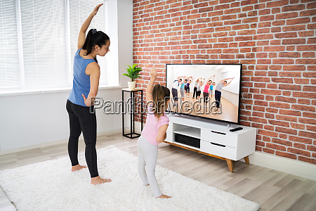 family doing home online stretching yoga