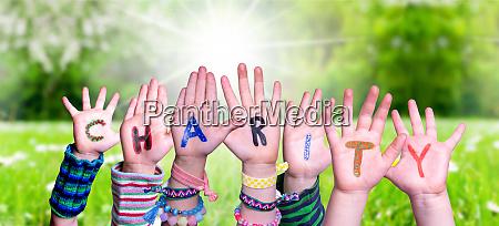 children hands building word charity grass