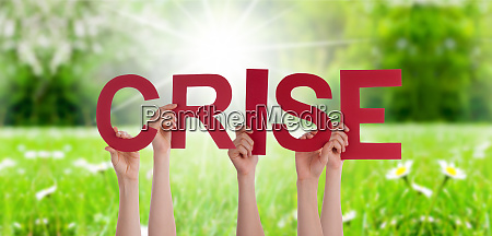 people hands holding word crise means
