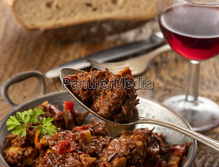 portion of austrian goulash on wood