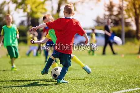elementary school kids playing football in