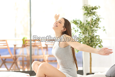 happy woman waking up outstretching in