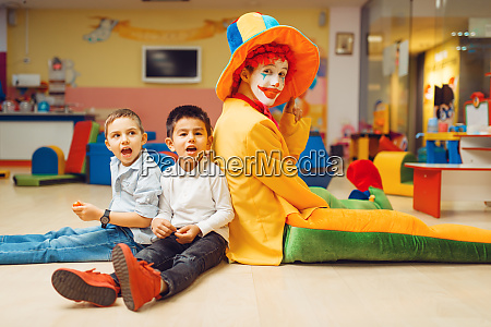 funny clown play with boys in