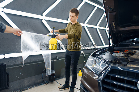 male workers wets template of car