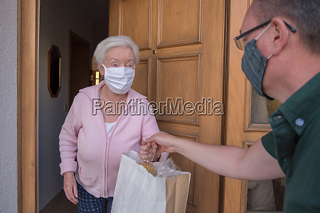 senior woman gets shopping bag from