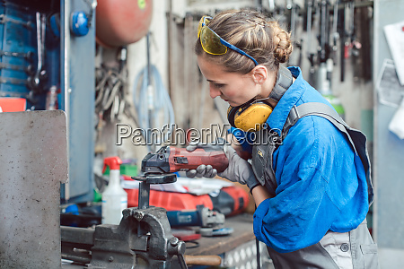 woman mechanic working with disk grinder