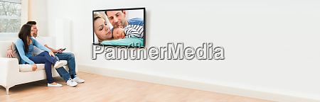 young couple in livingroom watching television