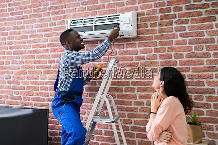 woman looking at technician repairing air