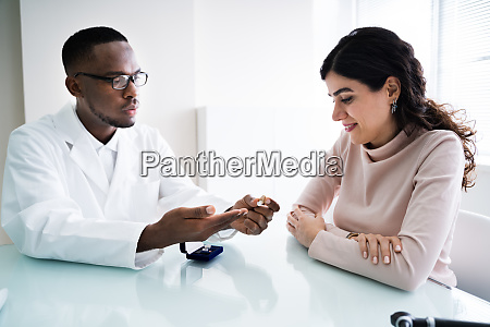 doctor showing hearing aid to patient