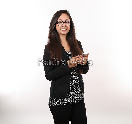 young lady smiles while holding phone