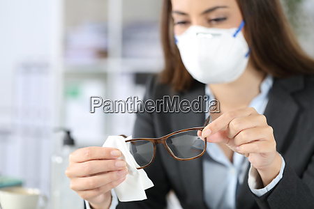 executive wearing mask disinfecting glasses with