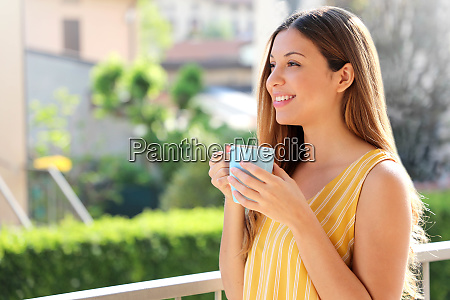 young woman relaxing on balcony holding