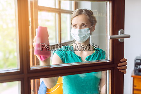 woman cleaning windows during covid 19