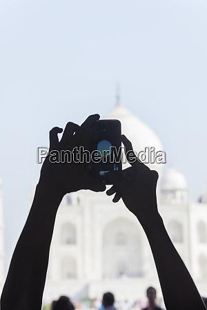 hands photographing the taj mahal