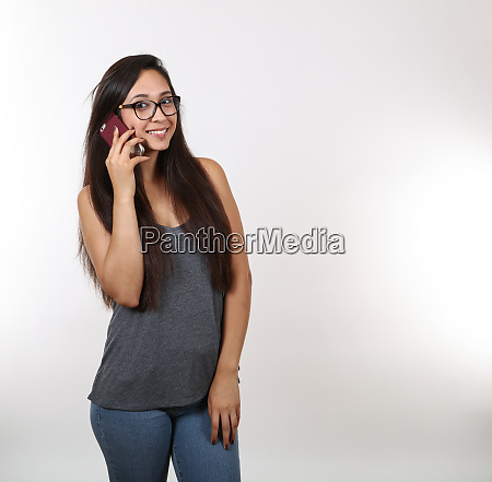 young girl wearing glasses talks on
