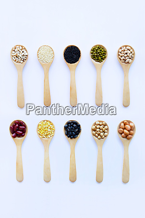 different beans legumes on wooden spoon
