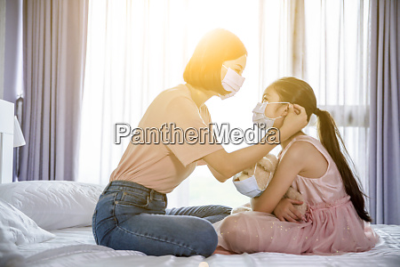 mother help daughter wearing medical mask