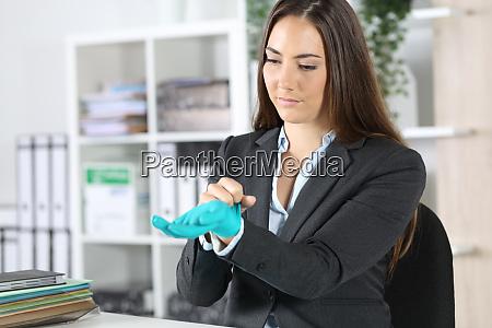 serious executive putting gloves avoiding covid