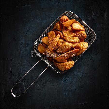 golden potatoes in metal basket
