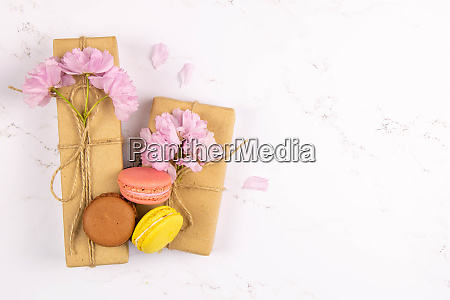 multicolored macaroons with peonies and gift