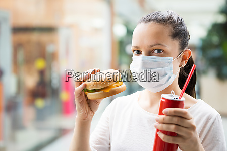 woman eating fastfood burger in face