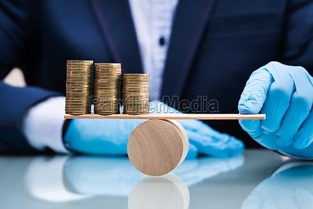 money and economy balance on seesaw