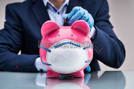 inserting coin in piggybank to save