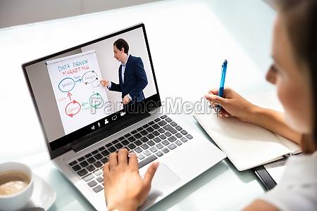 businesswoman reading information on laptop