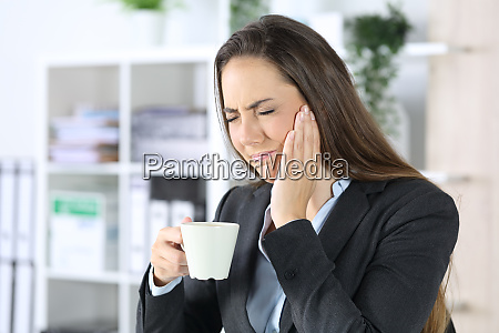 executive with toothache holding coffee at