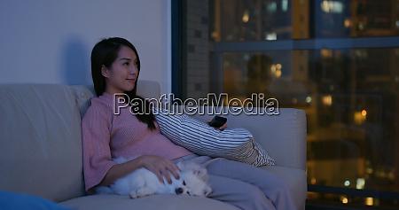 woman watch tv with her pomeranian