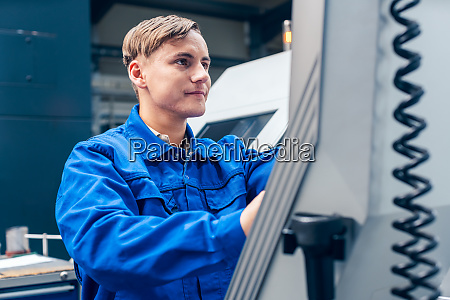 young worker programming lathe machine in