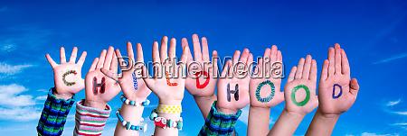 children hands building word childhood blue