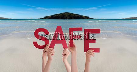 people hands holding word safe ocean