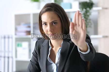 serious executive woman gesturing stop at