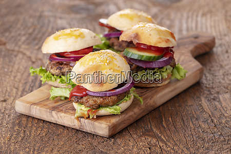 four small hamburges on a board