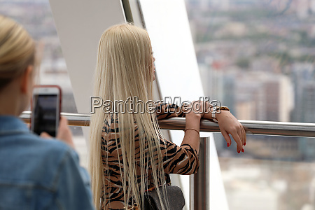 woman photographing a blonde woman