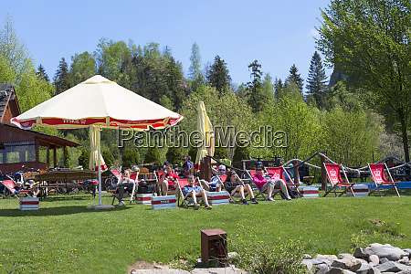 tourists resting on sunbeds on the