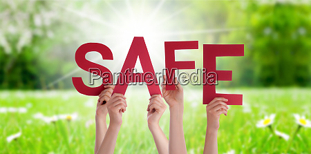 people hands holding word safe grass