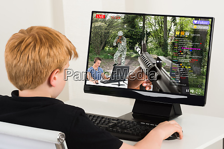 boy playing action game on computer