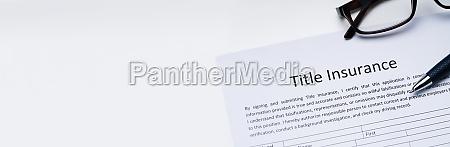 title insurance form over white desk