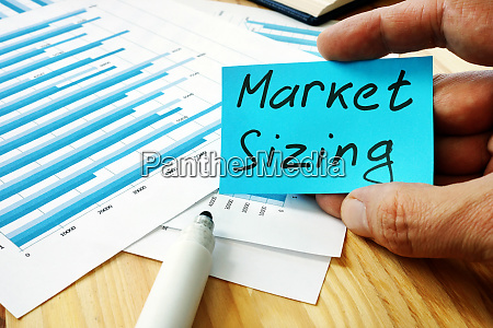 hand is holding market sizing inscription