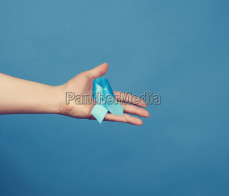 female hand holds blue silk ribbon