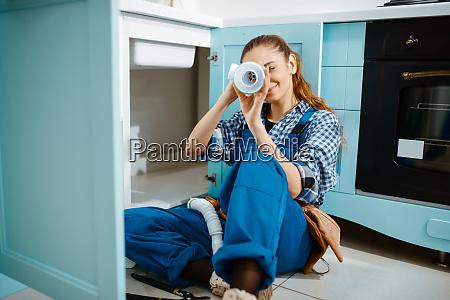 female plumber lying on the floor