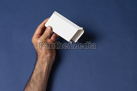 male hand holding an empty pillbox