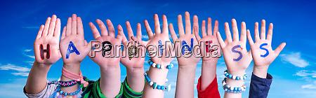 children hands building word happiness blue