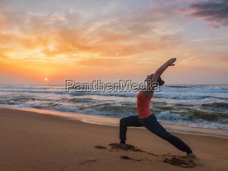 woman doing yoga asana virabhadrasana 1