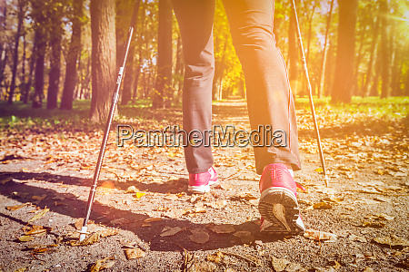 woman nordic walking outdoors feet close