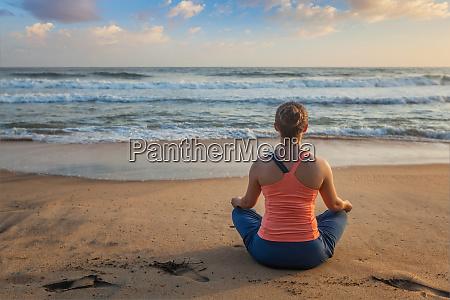woman doing yoga oudoors at beach