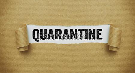 torn paper revealing the word quarantine